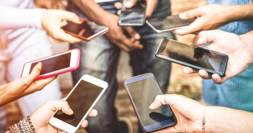 group holding smartphones
