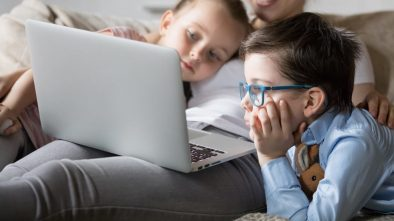 Mum and 2 kids watching a movie on a laptop